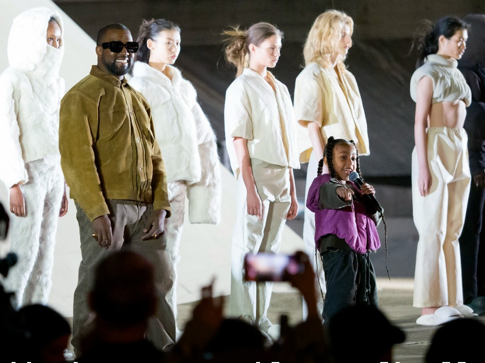 """Kanye West stands on stage during the """"Yeezy Season 8"""" show at Paris Fashion Week in March 2020"""