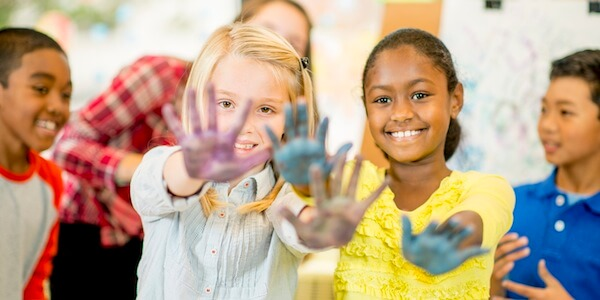 A group of elementary school aged children painting with their hands in a summer school / art resource setting, with a teacher / instructor helping.