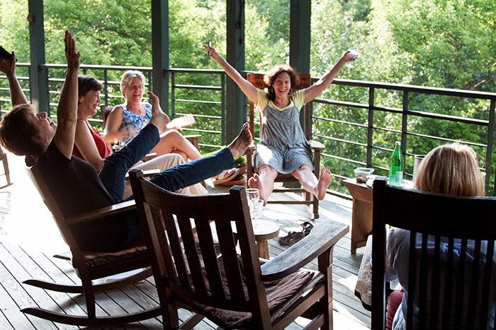 Group of female guests laughing on the porch
