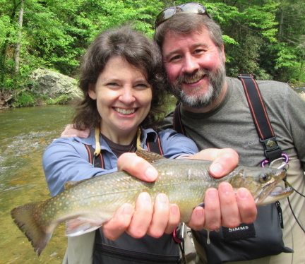 A couple holds a fish they caught fly fishing