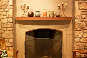 An inviting hearth with pottery on the mantle