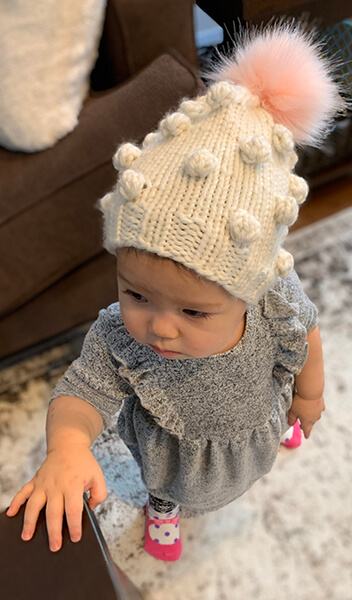 Little toddler girl wearing bobble hat with pink pom-pom.