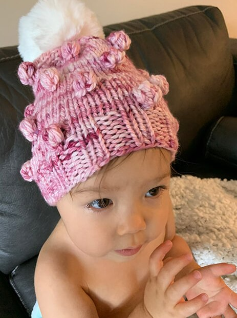 Little girl wearing a bobble hat