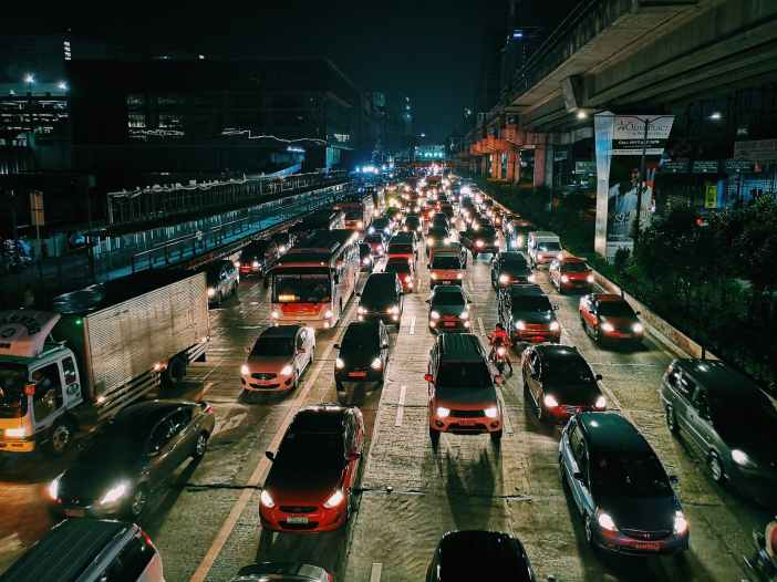 photo of vehicles on road during evening