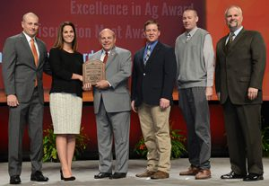 Madison County young farmers Stewart and Kasey McGill, left, accept their award as one of four finalists for national Achievement Award from AFBF President Zippy Duvall, national Young Farmers and Ranchers Chair Cole Coxbill of Wyoming, Dave Henderson of Case IH and Roger Phelps of Stihl.