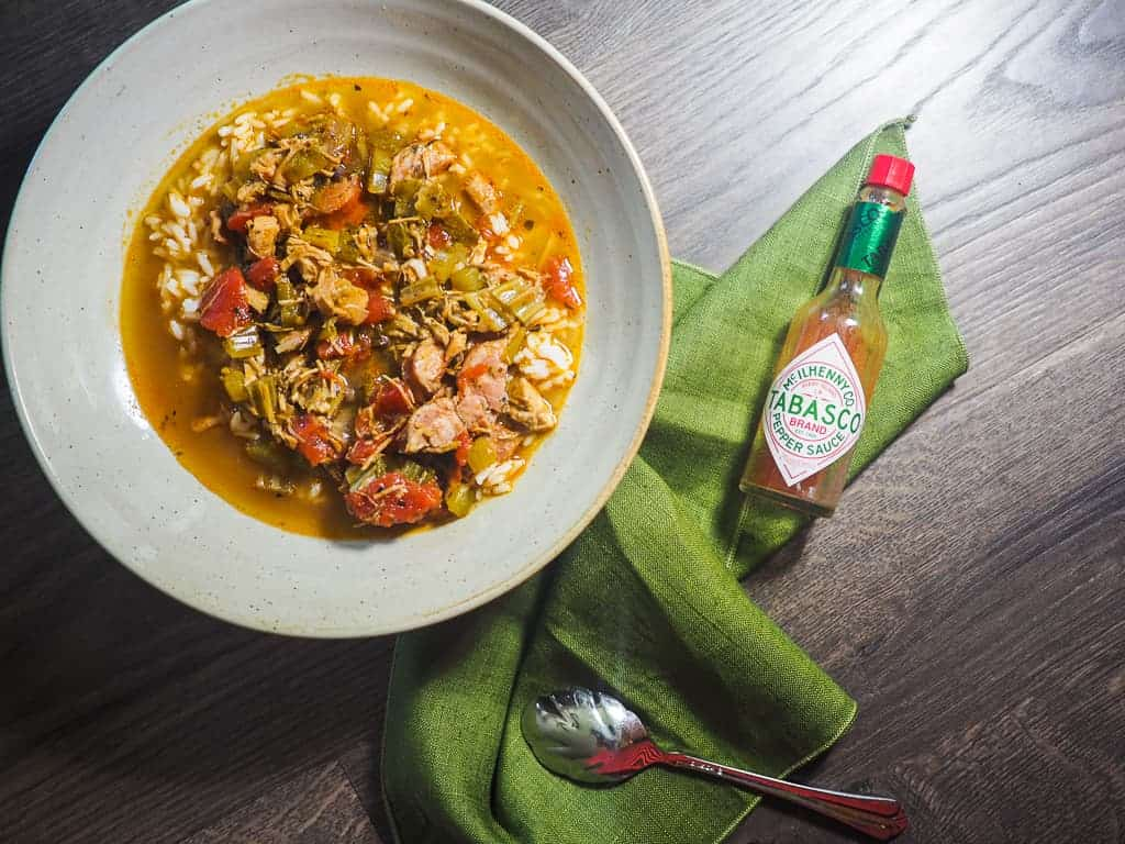 A white bowl of gumbo and a green napkin with a bottle of tabasco sauce on a wood background.