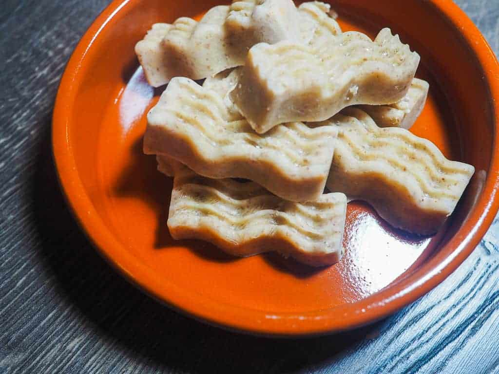A brown bowl with frozen peanut butter dog treats shaped like bacon.