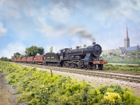 """A Drummond T14 4-6-0 """"Paddlebox"""" 461 a NuCast kit heads towards London with a Meldon Quarry Ballast train. The SR Diagram 1774 40T hoppers are modified LIMA wagons on new bogies and other details. Salisbury Cathedral can be seen in the background"""