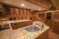 An enclosed helm on the bridge frees up the forward main-deck space for a thoughtfully laid-out galley and country kitchen, with plentiful storage and a premium view. As on all Marlow yachts, wood grains are matched perfectly as befits a custom build of this caliber. Photo: JLambertPhotos.com