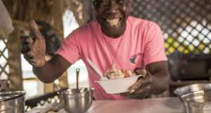 A man hands out a bowl of freshly made conch salad Bimini Eats Bahamian Gastronomy