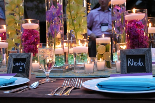 Glass cylinders filled with flowers water and floating candles