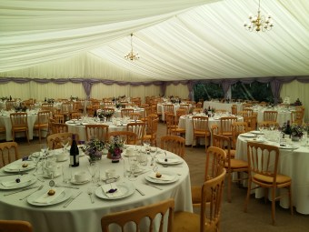 A beautiful marquee with lilac swags and pretty flower decorations on the tables.