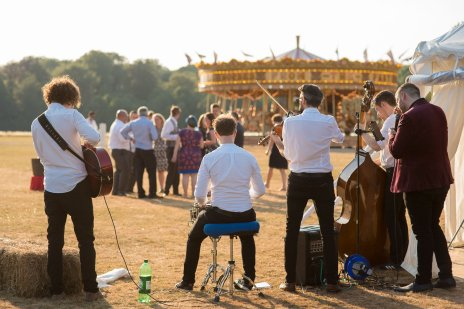 The wedding guests make the most of the balmy evening, enjoying the carousel and live music on the lawn at Stansted House. Photograph credit to Hana Venn Photography.