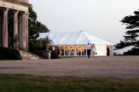 Evening guests stroll towards the welcoming wedding marquee ...