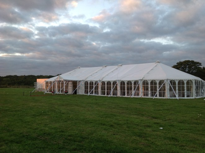 The sun sets over the fields and casts a warm glow across the length of the wedding marquee in this Hampshire vineyard ...