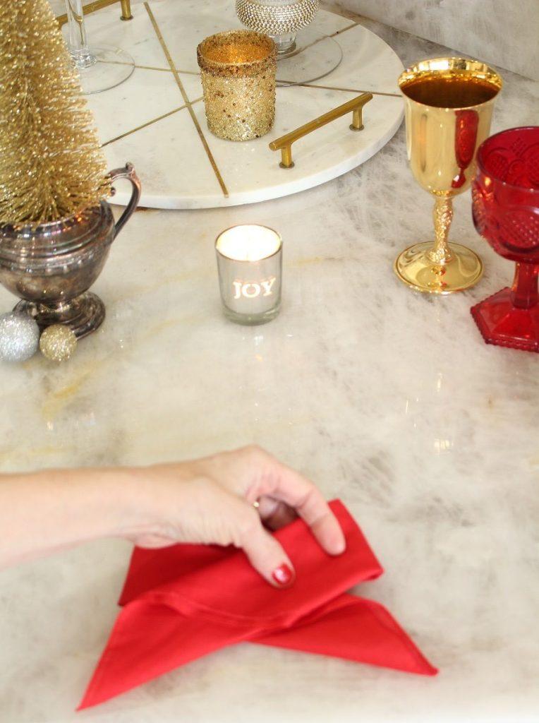 Hand folding red napkin