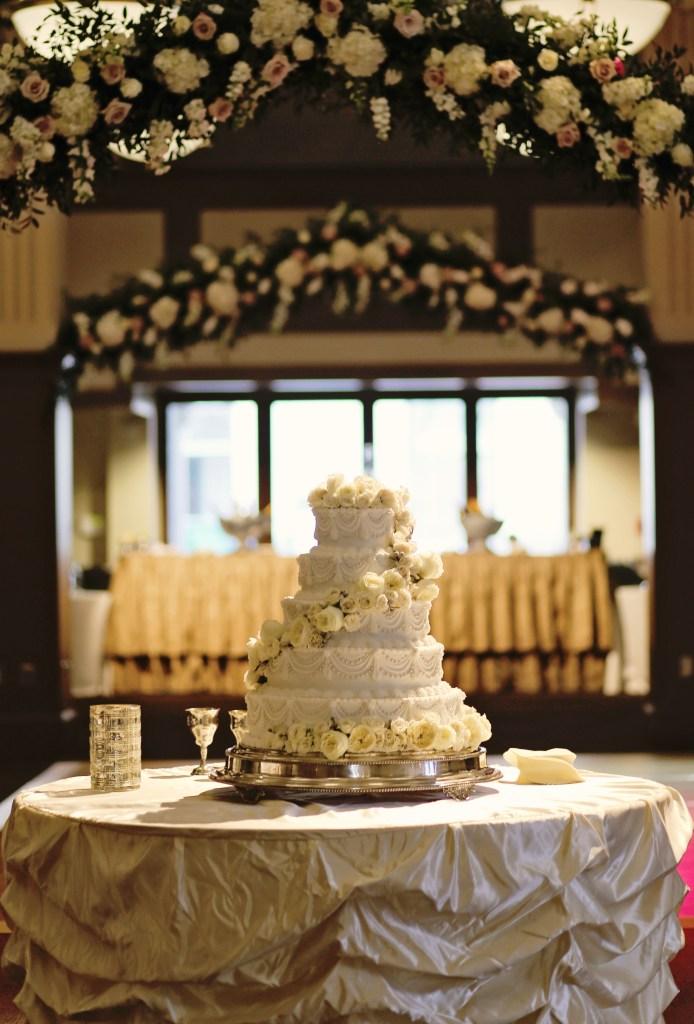 fresh flower arbor | floral arbor above wedding cake | msu riley center meridian ms | elegant wedding cake with fresh flowers | wedding flowers meridian
