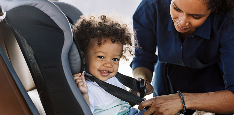 Child being buckled in car seat