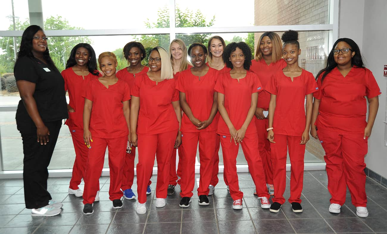12 women stand together. 11 wear red scrubs, one wears black scrubs.