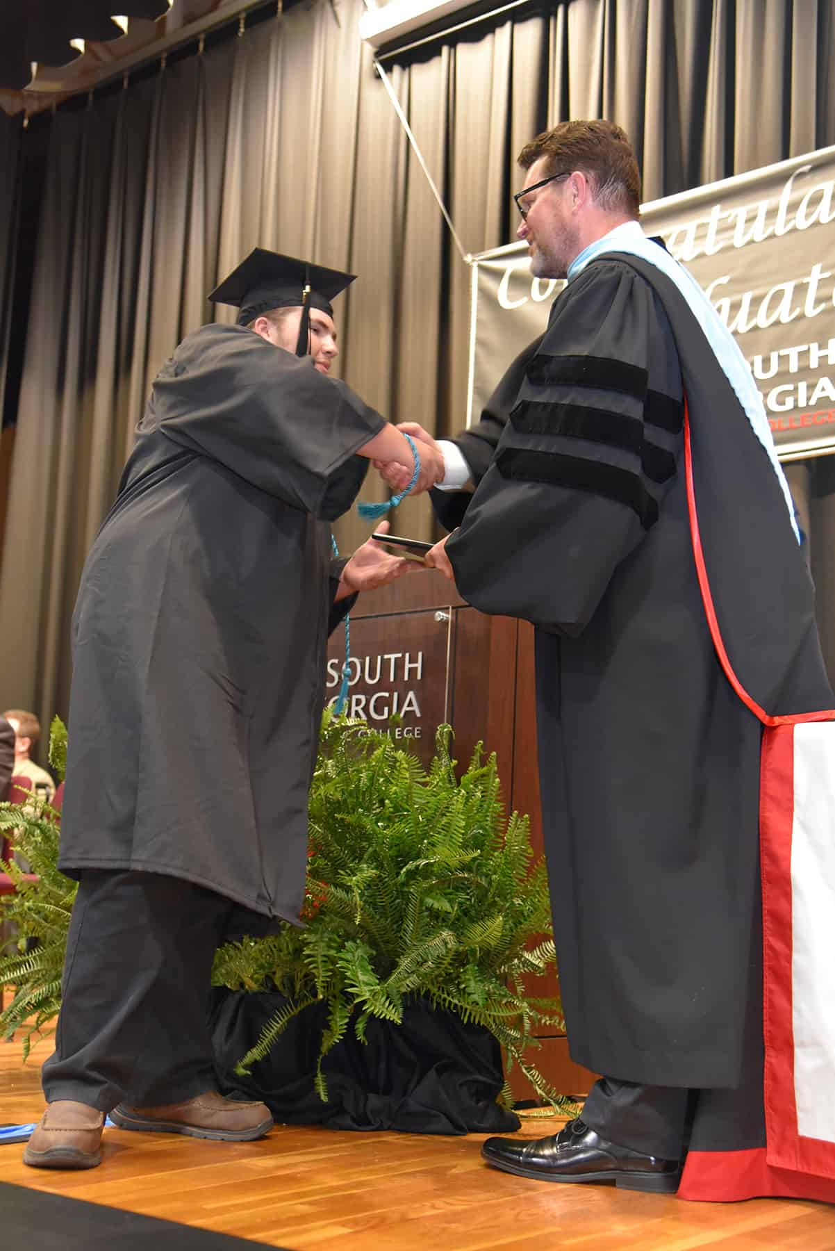 A student wearing a black graduation cap and gown accepts a diploma from a man.