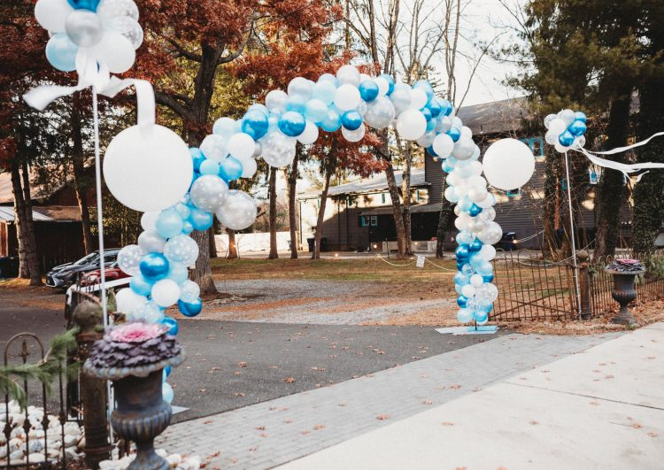 Blue and white balloon arch over drive to parking lot
