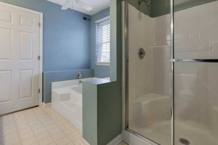 Stall shower has two seats and glass sliding door