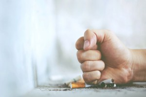 man's fist crushing cigarettes on table
