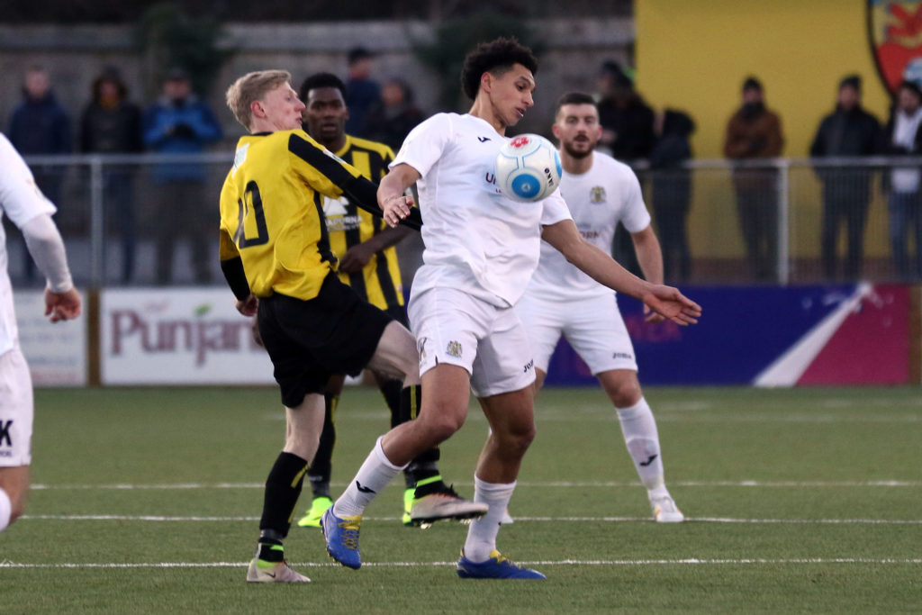 Lewis Montrose battles for the ball for Stockport