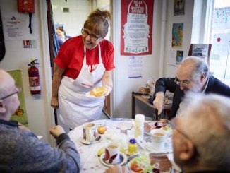 Kim Hyde, volunteer lead at Age UK Manchester, chats to service users in the cafe