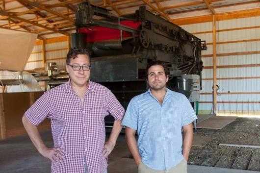 Pat Libutti, left, and Marcos Ribeiro inside the storage and processing barn at Craft Master Hops in Mattituck, with the 10,000-pound harvester they had shipped from Germany. Photo: Katharine Schroeder