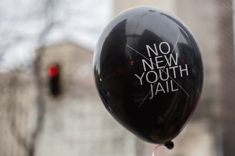 """A black balloon floats, donning in all-caps, """"No New Youth Jail"""" with a thin-lined """"X"""" through the words"""