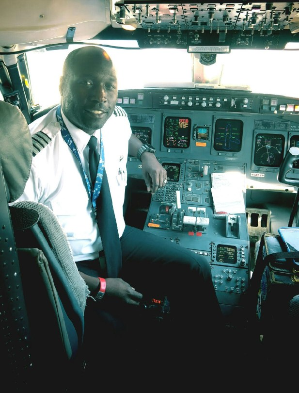 A black pilot in uniform sits in an airplane cockpit turned around in his seat to face the camera; flight instruments pepper the scene