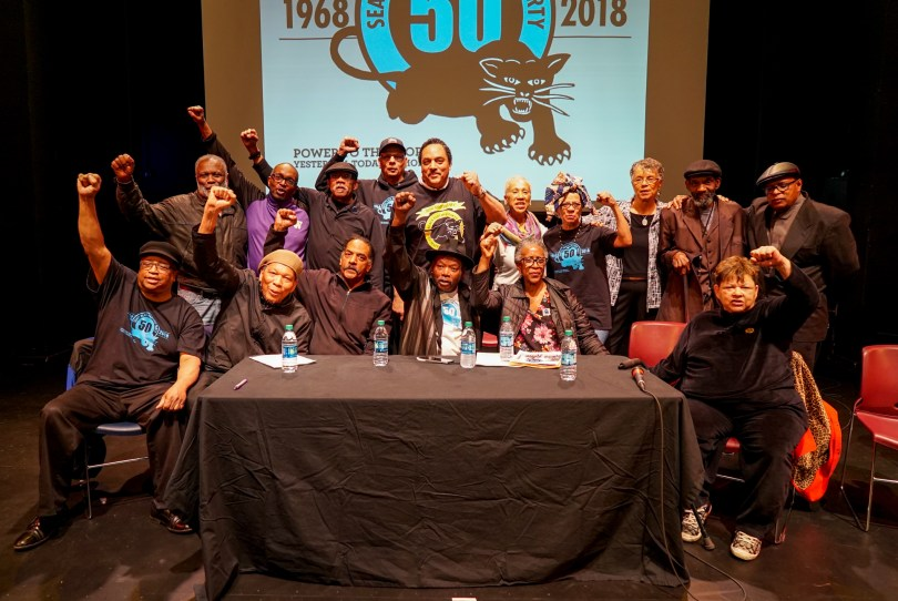Sixteen community elders of color on stage with a Black Panther 50th Anniversary image projected on a screen behind them; most of them have raised fists and wear black