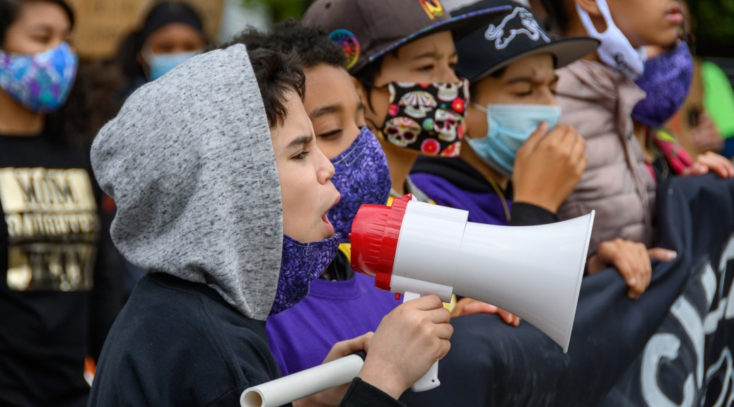 Seattle Children's March youth leader Ori leads a chant on the bullhorn.
