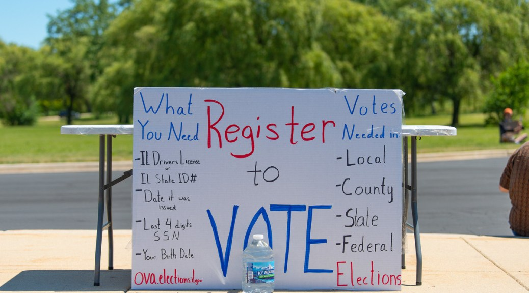 "White hand-made poster board sign with the words ""Register to Vote"" written on it leans against a folding table on a sidewalk. The sign has other information written on it about registering to vote and voting."