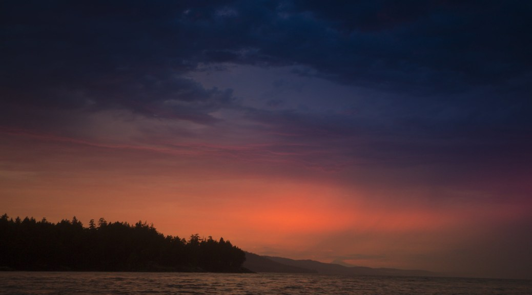 The horizon at sunrise or sunset looking out over a body of water; the scene is dark with grey-blue clouds above a fiery glowing fog in the distance; a small piece of land covered in silhouetted evergreens juts out from the left (and more can be seen in the distance).
