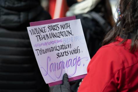 "A person attending the vigil holds a purple handmade sign with the words ""Violence starts with dehumanization, dehumanization starts with language"" written in elegant handwriting.  (Photo: Chloe Collyer)"