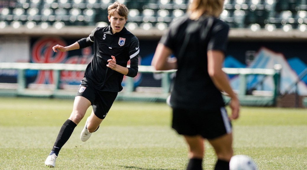 Transgender soccer player rushes toward another player on field.