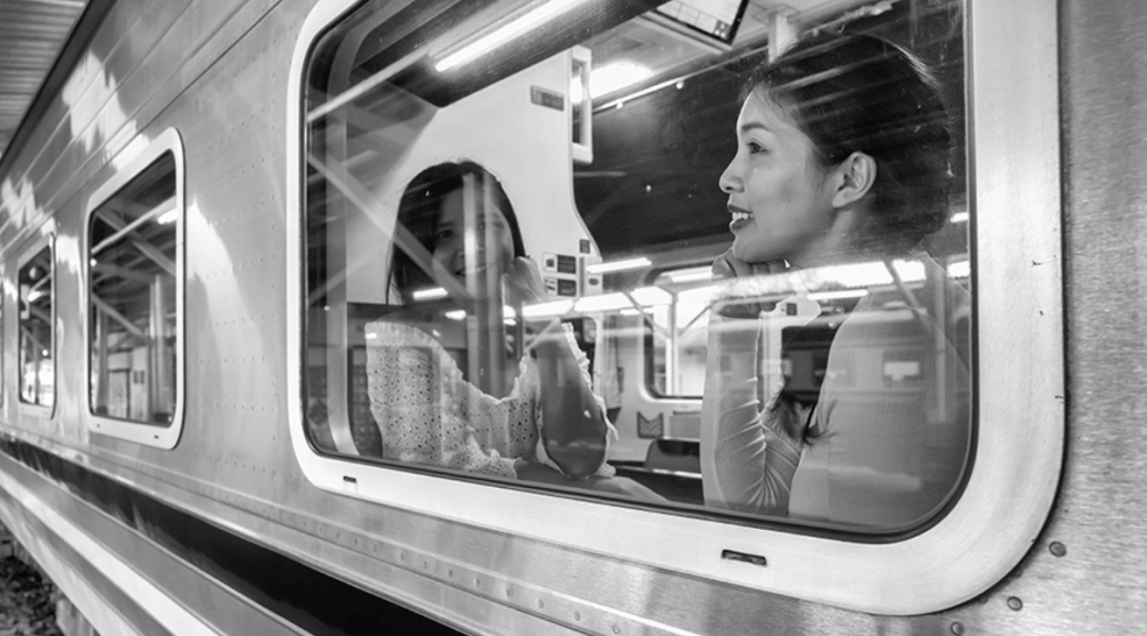 Two female-presenting individuals look happily and longingly out a subway train window