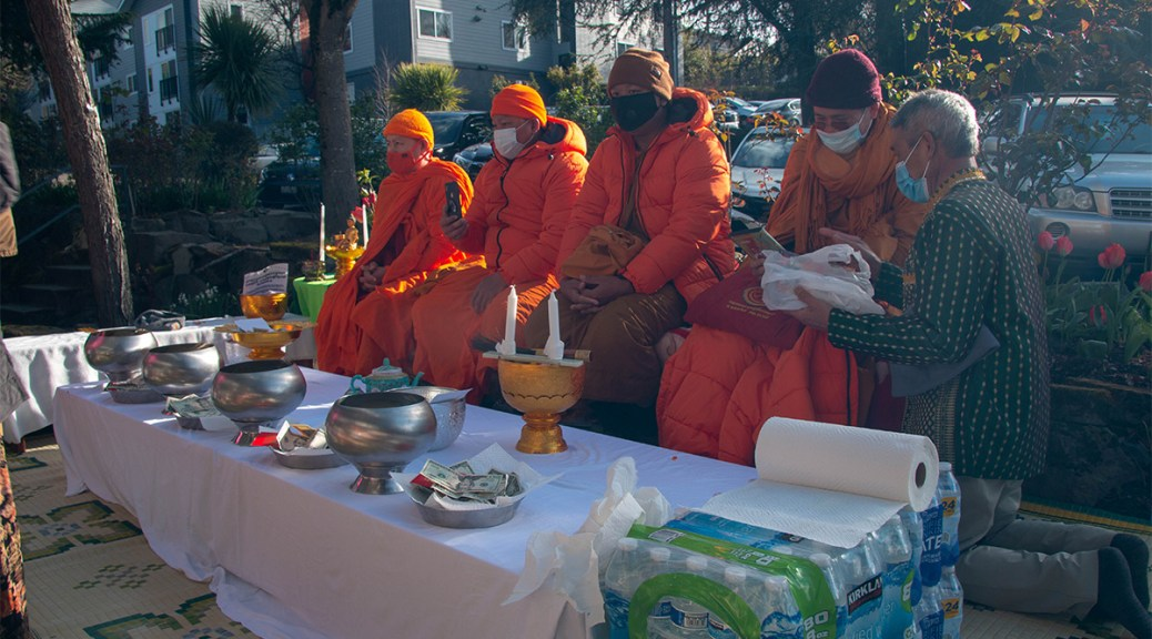 Buddhist Monks from Watt Dhammackakaram sit as residents of Mt. Baker Village chant in ceremony.