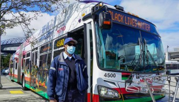 Artist and Metro transit operator Robert L. Horton stands in front of a Metro bus with his Black Lives Matter artwork