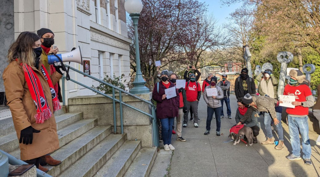 Two protestors stand in front of Franklin High School building steps with megaphones and speak to a crowd of protestors/teachers wearing red.