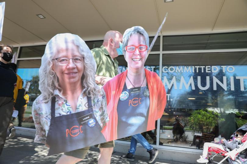 A demonstrator carries a cutout of Donna Rasmussen and Laurae McIntyre during an Apr. 14, 2021 protest at the Columbia City PCC