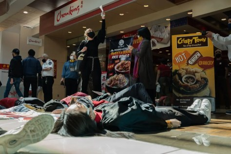 Filipino American activists participate in a die-in and lead chants at the Seafood City entrance inside the Southcenter Mall in Tukwila.