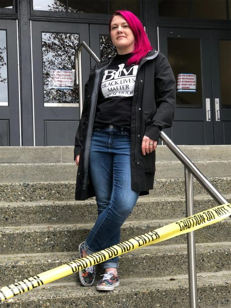 "Photo of Joy Springer standing on the steps of a school wearing a ""Black Lives Matter in School"" t-shirt."
