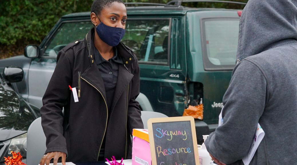"""Black-presenting individual with mask assists another at a table with a chalkboard that reads """"Skyway Resource Center."""""""