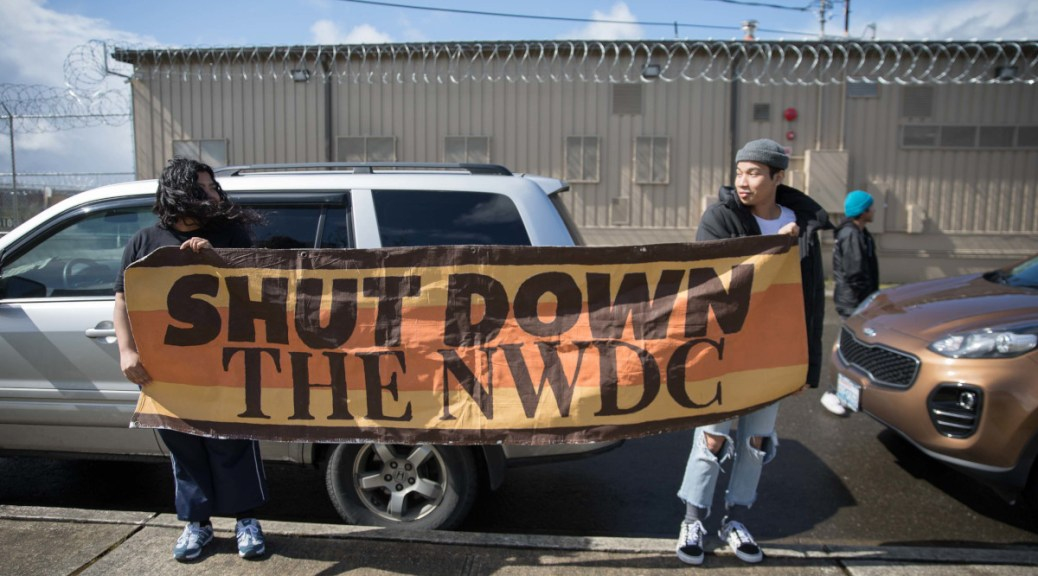 "Two protestors hold a sign that reads ""Shut down the NWDC"" in front of the barbed-wire fence of the NWIPC in Tacoma"