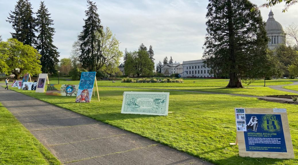 "Featured Image: Artwork from the ""Invest In Us"" pop-up art installation in Olympia, with work from artists (left to right): Jacob Johns, Mari Shibuya, West McLean, barry johnson, Young Women Empowered (Y-WE) Create, Dujie Tahat, and Nick Leppmann. Organized by Balance Our Tax Code, the exhibit features artwork in support of legislation to create a capital gains tax in Washington (SB 5096). Photos and videos of all the artwork on display can be viewed here)."