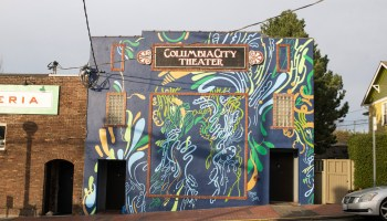 """""""Flourish Together,"""" a blue mural with yellow, white, orange, and green flourishes by Moses Sun adorns the exterior of the Columbia City Theater building"""