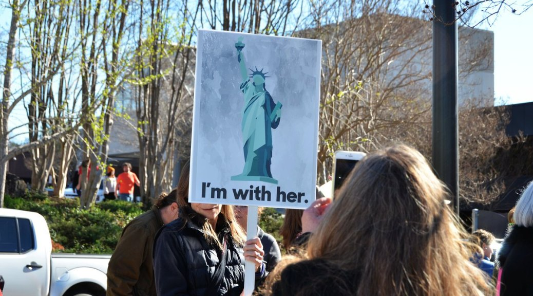 photo of woman holding I'm with her sign with image of the Statue of Liberty